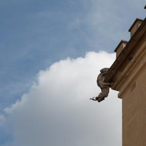 Reggio Emilia, Italy, May 2014: A gargoyle acting as a rain spout dangles off of a building.