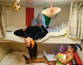 MV World Odyssey, 2016. The Cirigliano twins hang out in their economy inside double room after class. Their room decor is inspired by their cultural backgrounds and athletic interests.